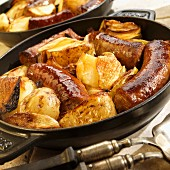 Swiss sausages with apples and onions in an iron pan