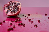 Half a pomegranate with seeds strewn around on a pink surface