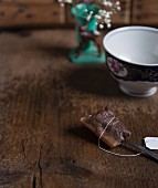 A used black tea bag on a wooden table in front of a tea cup