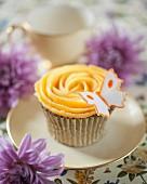 A cupcake with peach buttercream