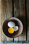 A whole egg and a cracked open eggs in a wooden bowl (seen above)