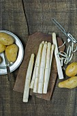 Fresh white asparagus with a peeler next to new potatoes