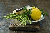 Wild asparagus, a lemon, Parmesan cheese and parsley in a bowl on a wooden board
