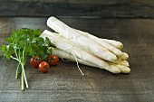 A bundle of fresh white asparagus on a wooden table