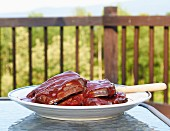 Raw beef ribs for grilling being marinated in barbecue sauce on a table outside