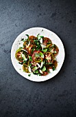Tomato salad with black tomatoes, shallots and herbs (seen from above)