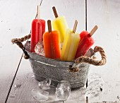 Various fruit ice lollies in a zinc tub of ice cubes
