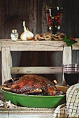 Roasted goose in a roasting dish with a glass of red wine next to it