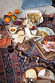 A picnic-style Christmas meal on a kilim rug with a cheese platter and roast ham