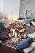 A picnic-style Christmas meal on a kilim rug with cushions and candles