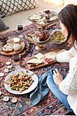 Weihnachtsmenü im Picknickstil auf Kelim mit Käseplatte, Salat und Schinkenbraten
