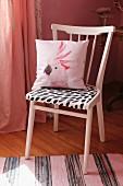 Upcycling: Rosa lackierter Küchenstuhl mit schwarz-weißem Sitzpolster und Kissen mit Kakadu-Abbildung