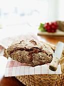A loaf of three-grain bread in a breadbasket