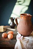 A rustic arrangement with a terracotta jug, eggs and butter
