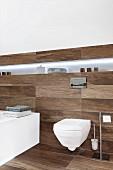 Modernes Hänge-WC und beleuchtete Ablagefläche in Designerbad, Fliesen in dunkler Dielenoptik