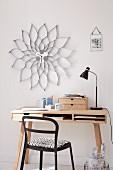 Nach klassischem Designer-Vorbild selbst gestaltete Wanduhr mit Blütenrahmen aus silberfarbener Wellpappe über kleinem Schreibtisch