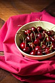 A bowl of cherries on a pink tablecloth