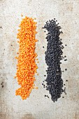 Red and black lentils on a stone surface