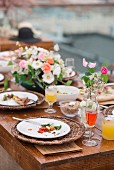 Empty plates on a festively decorated table with a large bunch of flowers