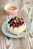 A mini Pavlova with berries and flaked almonds