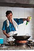 A cook with a wok in a restaurant kitchen (Bangkok, Thailand)