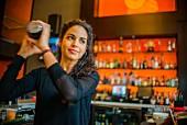 Junge Frau beim Schütteln eines Cocktailshakers in einer Cocktailbar