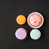 Four macaroons on a black background