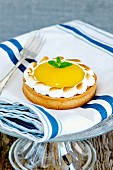 A lemon meringue tartlet on a cake stand