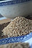 A pile of sesame seeds between oriental crockery