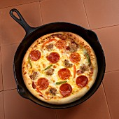 A pan pizza with sausage and peppers