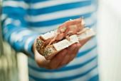 A boy holding a bacon sandwich