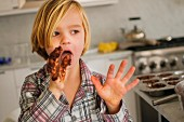A little boy licking chocolate cake mixture from his fingers