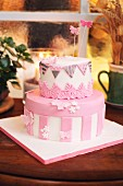 A pink and white birthday cake decorated with fondant butterflies