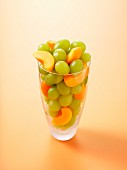 Grapes and apricot wedges in a glass on an orange surface