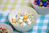 Sugar pearls and sugar sprinkles in a paper case
