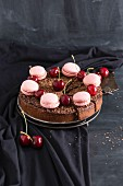 Chocolate and cherry cake decorated with pink macaroons