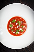 Cold tomato soup with mozzarella and pesto (seen from above)