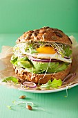 A sandwich with a fried egg, avocado and bean sprouts