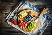 Gesunde belegte Brote mit Früchten auf Holzbrett