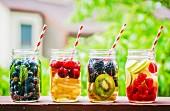 Vier fruchtige Drinks in Schraubgläsern auf Gartentisch