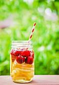 Eistee mit Früchten im Schraubglas mit Strohhalm auf Gartentisch