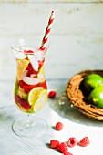 Eistee mit Früchten im Longdrinkglas mit Strohhalm