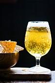 Ein Glas helles Bier und Tortillachips