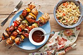 Chicken skewers with peppers and onions, and a bowl of orzo