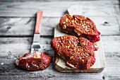 Spiced beef steaks on a chopping board