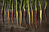 A row of colourful carrots on a wooden surface