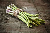 A bunch of green asparagus on a wooden board