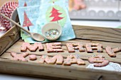 Alphabet biscuits with colourful sugar sprinkles spelling festive message on wooden tray