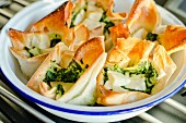 Filo pastry packets filled with feta cheese and spinach (Greece)