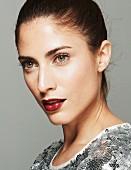 Brünette Frau mit Hochsteckfrisur und Paillettenshirt, Lippen dunkelrot geschminkt